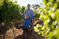 Man pushing his cheerful girlfriend in wheelbarrow at vineyard Stock Image