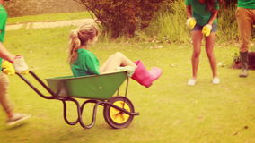 Man pushing his friend in wheelbarrow with friends behind stock video