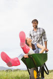 Man pushing his girlfriend in a wheelbarrow Stock Photos