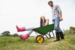 Man pushing his girlfriend in a wheelbarrow Stock Photography