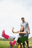Man pushing his girlfriend in a wheelbarrow Royalty Free Stock Image