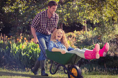 Man pushing his girlfriend in a wheelbarrow Royalty Free Stock Photography