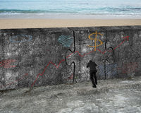 Man pushing huge puzzle door of business doodles concrete wall. Man pushing huge puzzle door of concrete wall with business concept doodles, on the sea beach Stock Photo