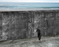 Man pushing huge puzzle door of concrete wall. With sea beach background Royalty Free Stock Images