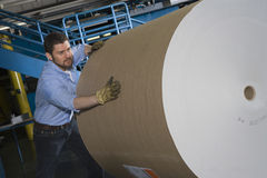 Man Pushing Huge Roll Of Paper In Factory. Man pushing huge roll of paper in newspaper factory Stock Images