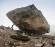 Man with pushing a huge stone in Ergaki mountains, Russia stock photography