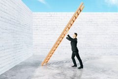 Man pushing ladder to wall Royalty Free Stock Photos