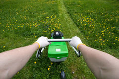 Man is pushing mover. Mowing a grass. View from gardener eyes royalty free stock photo