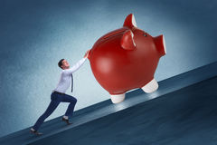 The man pushing piggybank uphill in business concept Royalty Free Stock Photography