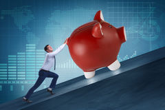 The man pushing piggybank uphill in business concept Stock Photography