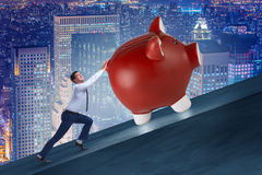 The man pushing piggybank uphill in business concept Stock Image