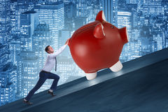 The man pushing piggybank uphill in business concept Stock Photo