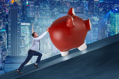 The man pushing piggybank uphill in business concept Stock Photos