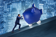 The man pushing piggybank uphill in business concept Royalty Free Stock Image
