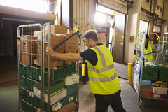 Man pushing a roll cage ready for delivery in a warehouse Royalty Free Stock Photography