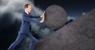 Man pushing rolling round rock royalty free stock image