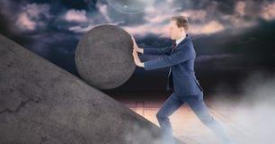 Man pushing rolling round rock stock photo