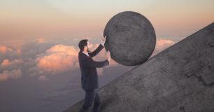 Man pushing rolling round rock royalty free stock photo