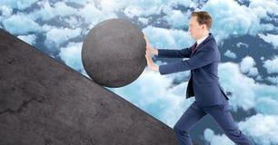 Man pushing rolling round rock stock image