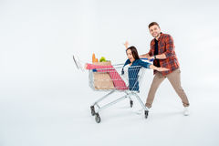 Man pushing shopping cart with excited woman and grocery bag on white Stock Images