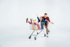 Man pushing shopping cart with excited woman and grocery bag on white Stock Image