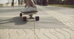 Man pushing a skateboard along a textured sidewalk stock footage
