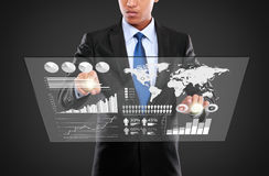 Man pushing on a touch screen of infographics stock photography