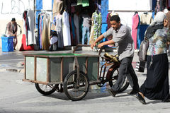 Man pushing a tricycles Stock Photo