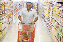 Man pushing trolley along supermarket aisle Stock Photo