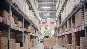 A man is pushing a trolley full of boxes on it between shelves with cardboard boxes in a storage warehouse. Slowly getting into focus stock video footage