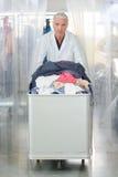 Man pushing trolley laundry Royalty Free Stock Image