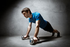 Man pushing up from the dumbbells on wall backdrop Stock Photo
