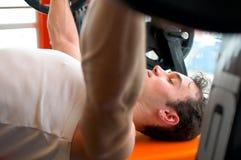 Man pushing up weights. Man at the gym laid down on the bench and pushing up weights royalty free stock image