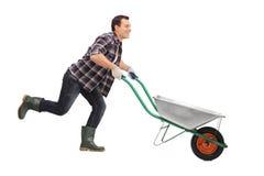Free Man Pushing Wheelbarrow And Running Royalty Free Stock Photos - 71220708