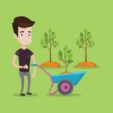 Man pushing wheelbarrow with plant. Stock Image