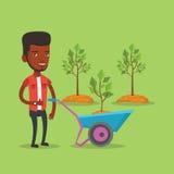 Man pushing wheelbarrow with plant. Royalty Free Stock Photos