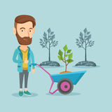 Man pushing wheelbarrow with plant. Stock Photo