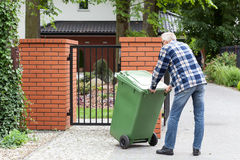 Man is pushing wheeled dumpster Royalty Free Stock Photography