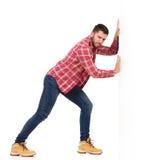 Man pushing a white wall Royalty Free Stock Photos