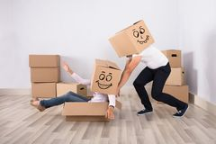 Man Pushing A Woman On Cardboard. Man Wearing Cardboard Box Pushing A Woman Sitting On Cardboard Box At Home royalty free stock photography
