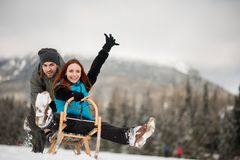 Man pushing woman down the hill on sledge. Excited young redhead women enjoying the sled ride stock photos