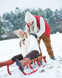 Man pushing woman on sled in winter Royalty Free Stock Photo
