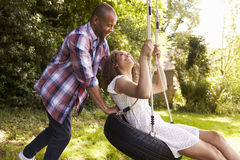 Man Pushing Woman On Tire Swing In Garden Royalty Free Stock Photography