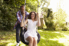 Man Pushing Woman On Tire Swing In Garden Stock Photography