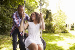 Man Pushing Woman On Tire Swing In Garden Stock Image