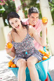 Man Pushing Woman In Wheelbarrow Stock Image