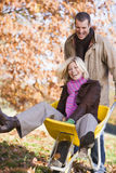 Man pushing woman in wheelbarrow Stock Photo