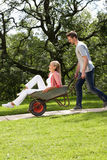 Man Pushing Woman In Wheelbarrow Stock Photos