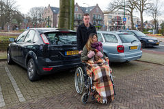 Man pushing a woman in a wheelchair at a car park. SOEST, THE NETHERLANDS - JAN 28: Man pushing a woman in a wheelchair at a parking place in a Dutch village on stock image