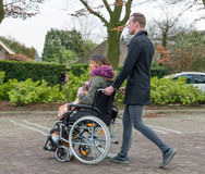 Man pushing a woman in a wheelchair at a car park. Man pushing a women in a wheelchair at a parking place in a Dutch village royalty free stock photos